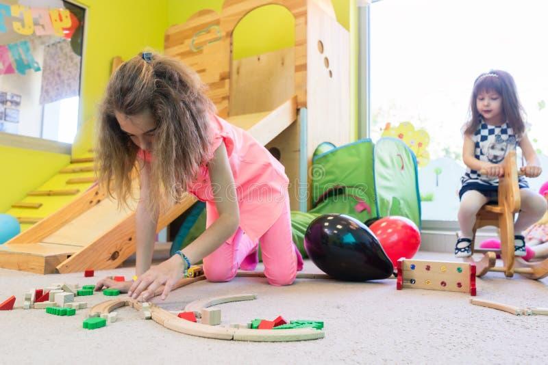 Gullig flicka som bygger en struktur i jämvikt under rast på dagiset royaltyfri bild