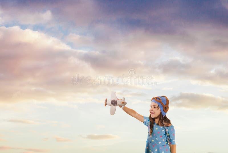Gullig flicka som drömmer av sommarferier med ett stuckit leksakflygplan fotografering för bildbyråer