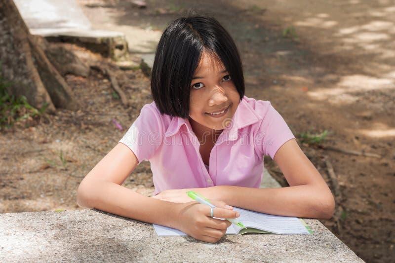 Gullig flicka som gör läxa i parkera royaltyfria bilder