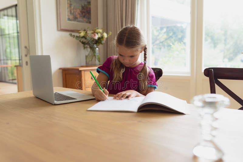 Gullig flicka som gör läxa på den äta middag tabellen i ett bekvämt hem royaltyfri fotografi