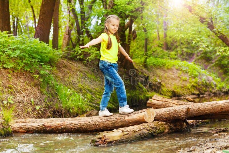 Gullig flicka som korsar floden i sommarskog arkivbild