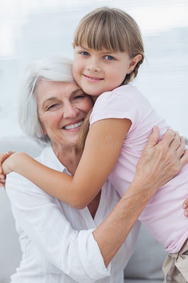 Gullig flicka som kramar hennes farmor arkivbilder