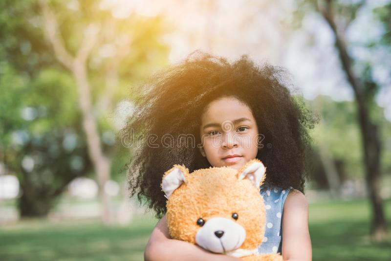 Gullig flicka som kramar nallebjörnen arkivfoton