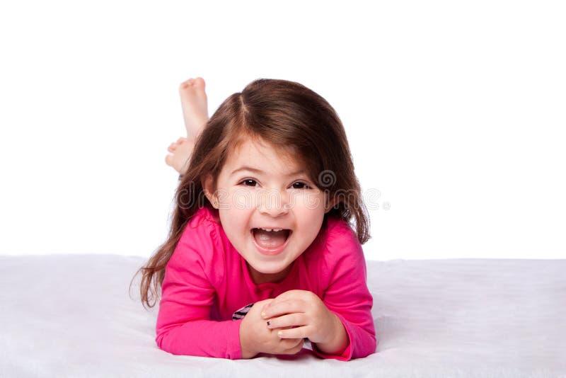 Gullig flicka som lägger på buk royaltyfri bild