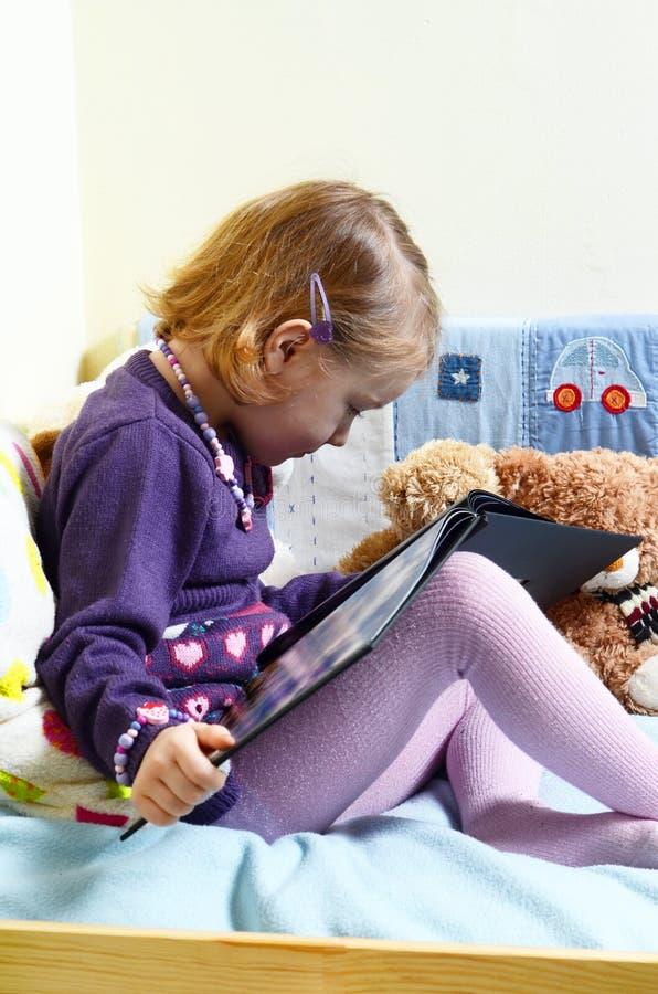 Gullig flicka som läser en bok på hennes säng med leksaker runt om henne royaltyfria foton