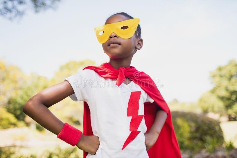 Gullig flicka som låtsar för att vara superhero med händer på höft royaltyfri foto