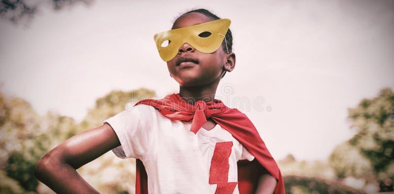 Gullig flicka som låtsar för att vara superhero med händer på höft royaltyfri fotografi