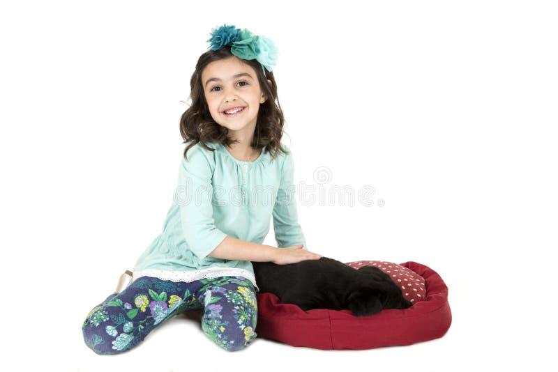 Gullig flicka som ler dalta en svart valphund arkivfoton