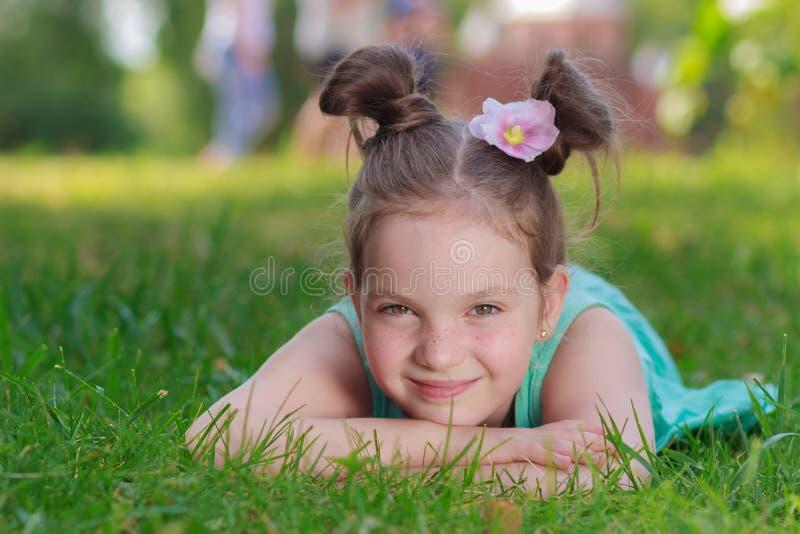 Gullig flicka som ligger på det gröna gräset, det fria, sommartid, suddig bakgrund royaltyfri fotografi
