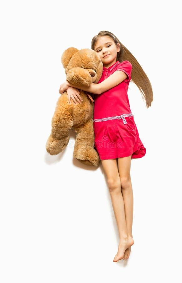 Gullig flicka som ligger på golv och kramar den stora nallebjörnen arkivfoto