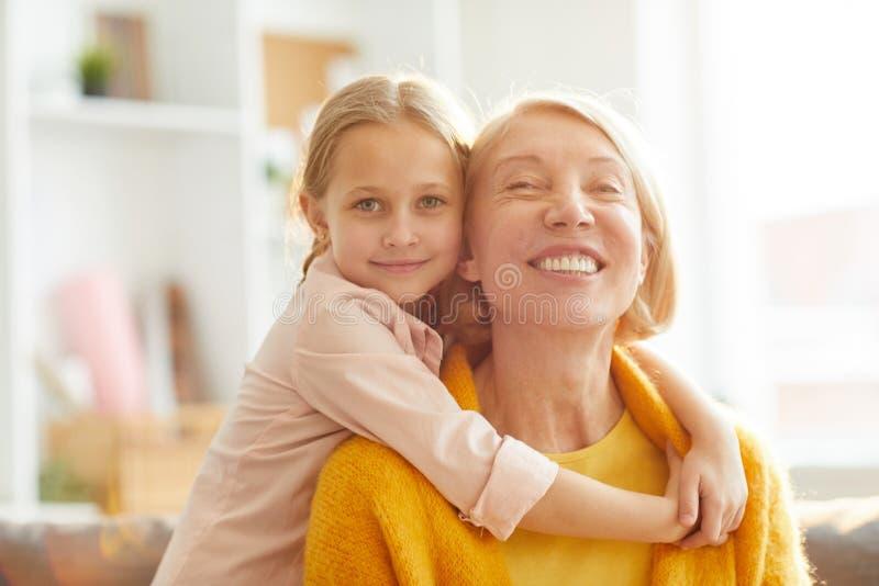 Gullig flicka som omfamnar mormodern arkivbild