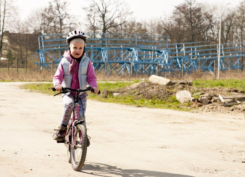 Gullig flicka som rider en cykel arkivbild