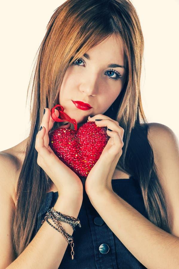 Gullig flicka som rymmer röd hjärta royaltyfri foto