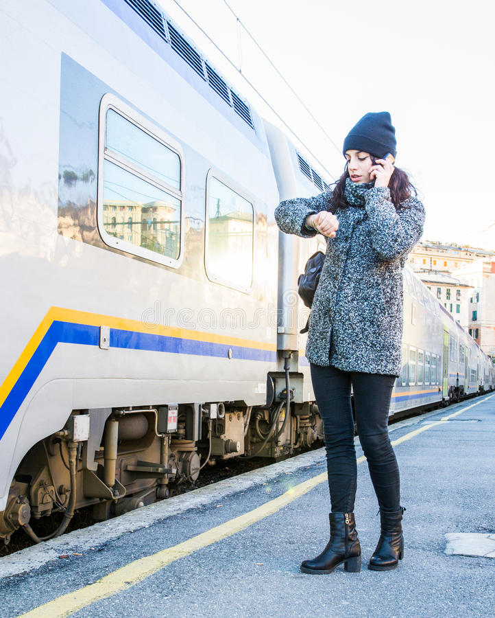 Gullig flicka som ser hennes klocka och talar på telefonen arkivfoto