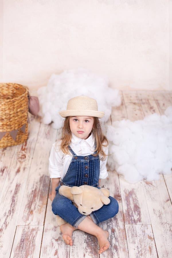 Gullig flicka som sitter i studion p? bakgrunden av en ballong, stj?rnor och moln och rymmer en nallebj?rn Lilla flickan ?r dreae arkivfoto