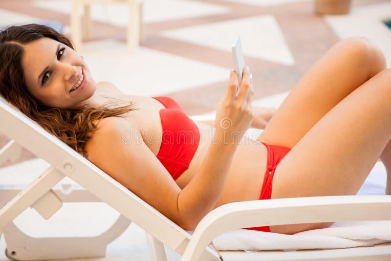 Gullig flicka som smsar vid pölen royaltyfri fotografi
