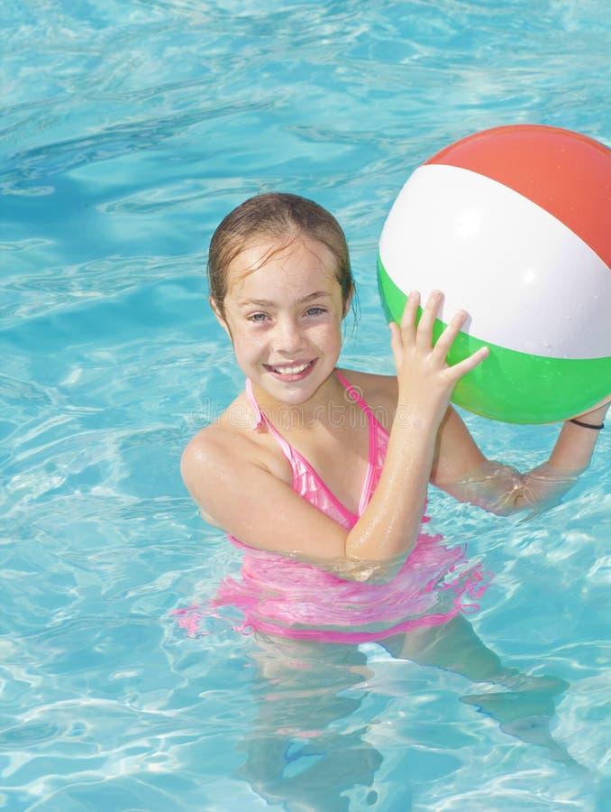 Gullig flicka som spelar i en simbassäng royaltyfri bild