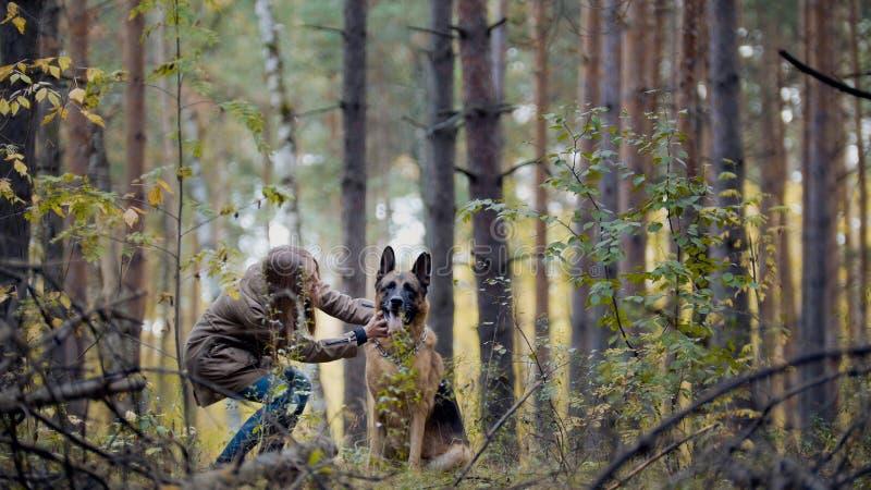 Gullig flicka som spelar med hennes husdjur - den tyska herden parkerar in royaltyfri foto