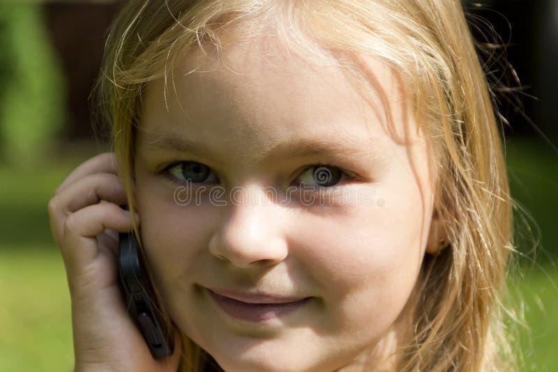 Gullig flicka som talar vid cell- arkivfoto