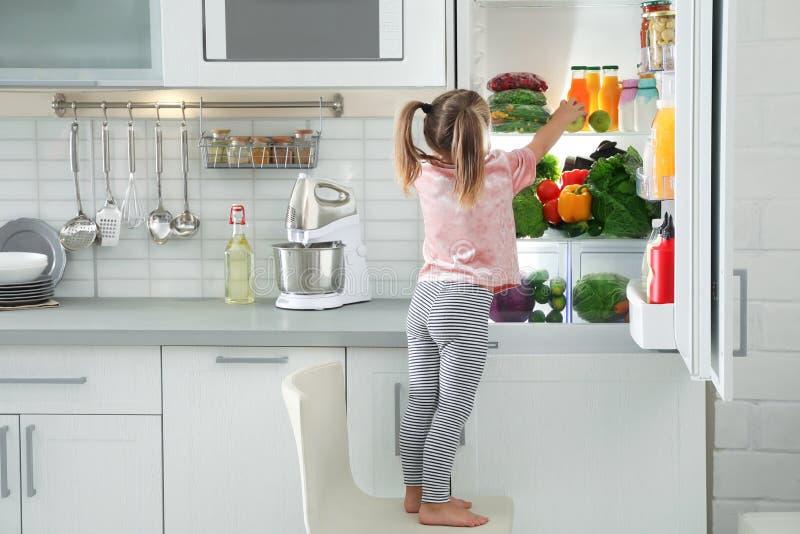 Gullig flicka som tar äpplet ut ur kylskåpet arkivbild