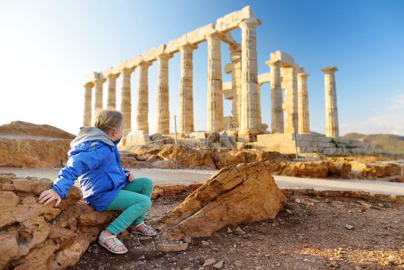 Gullig flicka som undersöker gammalgrekiskatemplet av Poseidon på udde Sounion, en av de viktiga monumenten av guldåldern av Aten royaltyfri bild