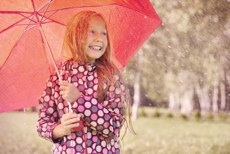 Gullig flicka under regn fotografering för bildbyråer