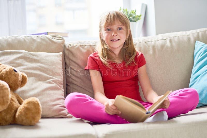 gullig flickaavläsning för bok arkivbild