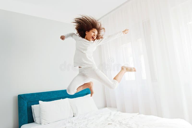 Gullig flickabanhoppning på sängen, lycka arkivfoton