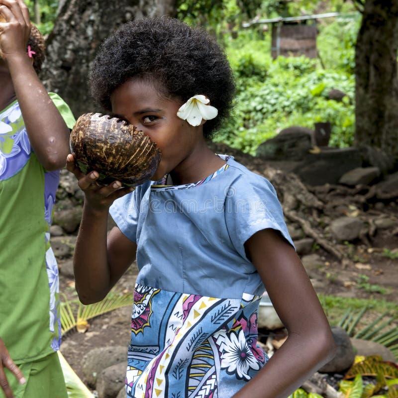 Gullig flickadrinkin från kokosnötskalet, gulligt tonårigt för Fijian med den enorma fragipaniblomman arkivbild