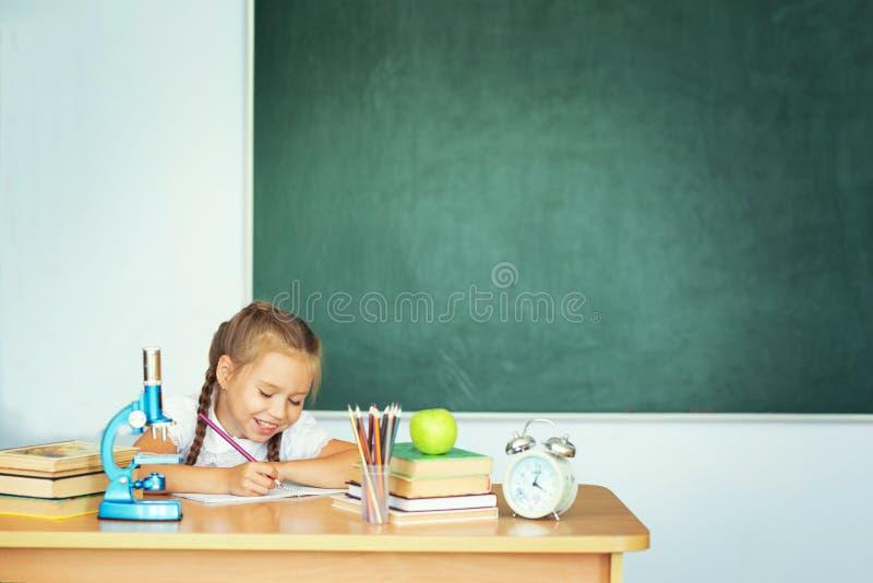 Gullig flickahandstil i anteckningsbok i klassrum på skolan Kopieringsutrymme för text på den gröna skolasvart tavla royaltyfri bild