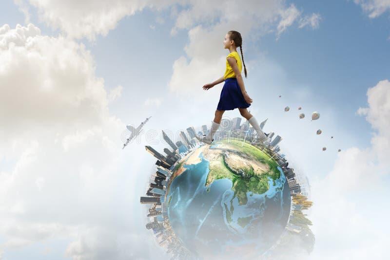Gullig glad liten flicka som går på jordklotet Blandat massmedia royaltyfri foto