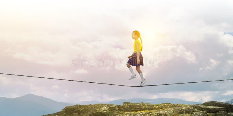 Gullig glad liten flicka som g?r p? ett rep ?ver stad Blandat massmedia royaltyfri bild