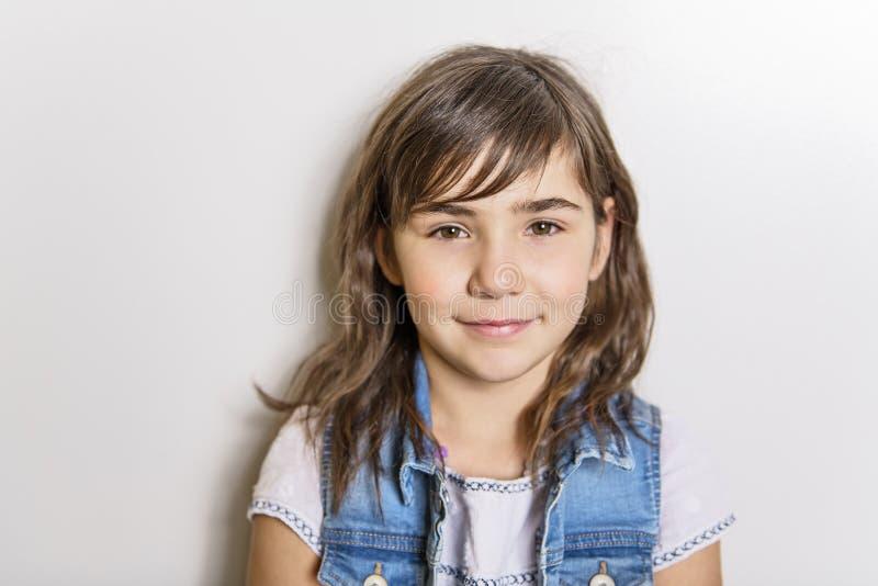 Gullig gladlynt liten flickastående som isoleras på grå bakgrund arkivbilder