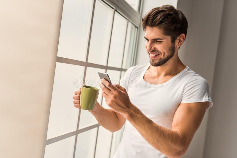 Gullig grabb som hemma använder mobiltelefonen royaltyfria foton