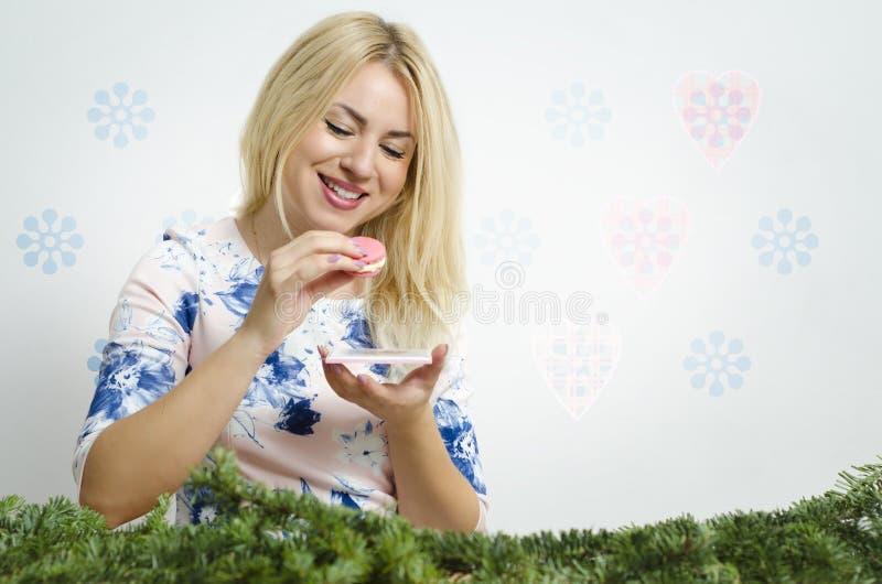 Gullig härlig blondin som äter den smakliga makronkakan royaltyfri fotografi