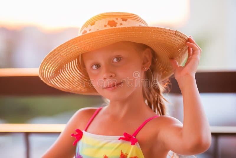 Gullig härlig liten flicka på havet på en solnedgångbakgrund St?ende av en flicka i en sugr?rhatt royaltyfri bild