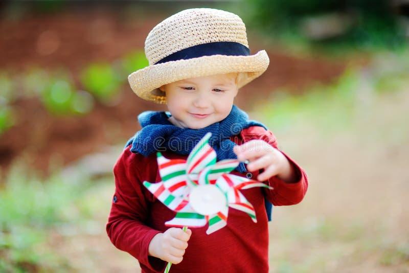 Gullig hållande leksakväderkvarn för litet barn royaltyfria foton