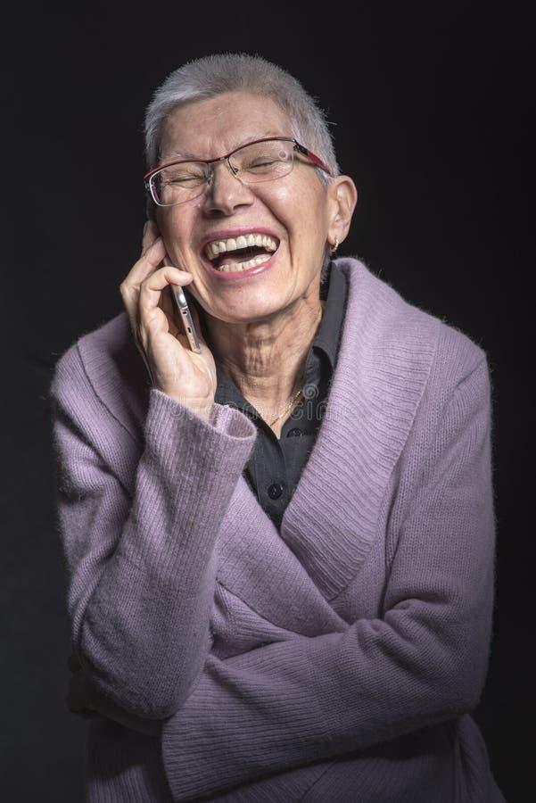 Gullig hög kvinna som tycker om ett telefonsamtal royaltyfri bild