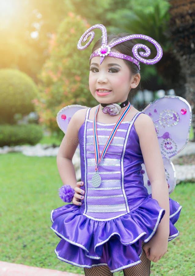 Gullig hejaklacksledare i den violetta feldräkten royaltyfri foto