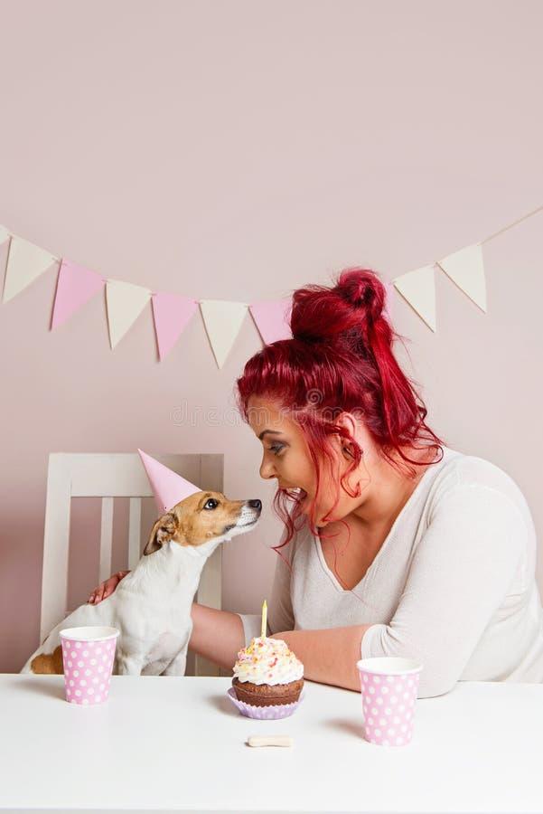 Gullig hund med hennes ägare som firar hennes födelsedag fotografering för bildbyråer