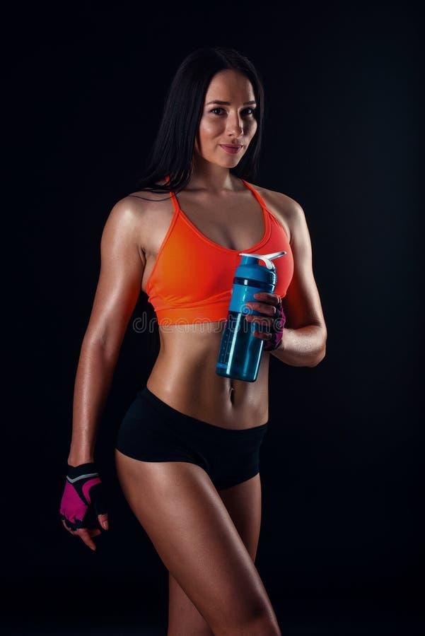 Gullig idrotts- flicka i sportswear som kopplar av efter genomkörare med shaker som isoleras över svart bakgrund Den sunda unga k arkivfoto