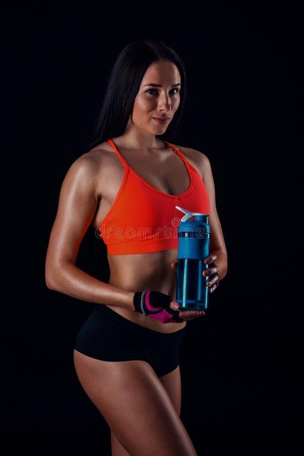 Gullig idrotts- flicka i sportswear som kopplar av efter genomkörare med shaker som isoleras över svart bakgrund Sunda drinkar fö arkivfoto