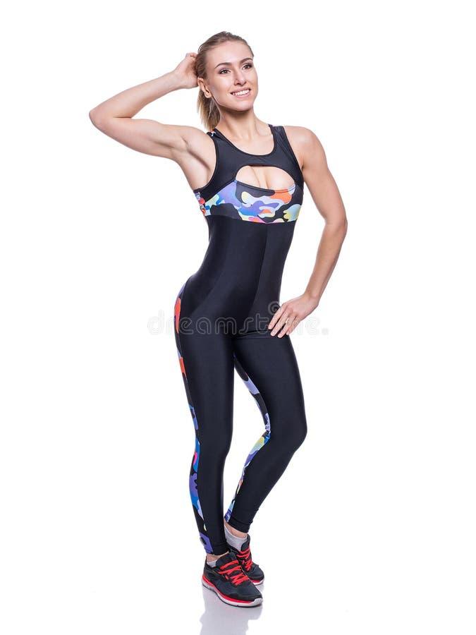 Gullig idrotts- flicka som poserar i studion som isoleras på vit bakgrund Sportswear för kroppsbyggare för ung kvinna bärande ell royaltyfria foton
