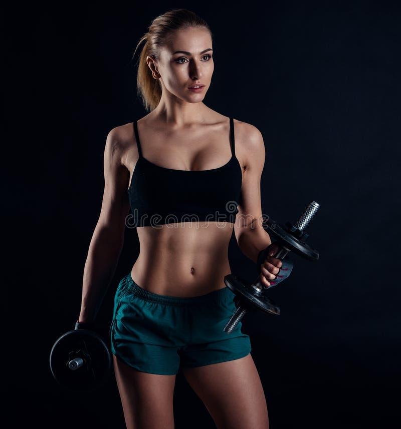Gullig idrotts- modellflicka i sportswear med hantlar i studio mot svart bakgrund Idealt kvinnligt sportdiagram fotografering för bildbyråer