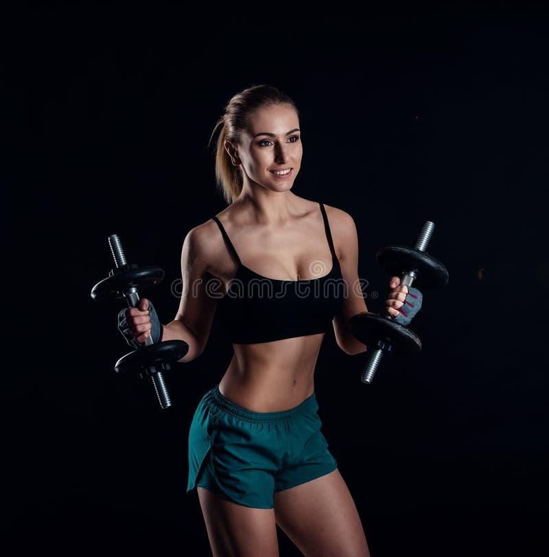 Gullig idrotts- modellflicka i sportswear med hantlar i studio mot svart bakgrund Idealt kvinnligt sportdiagram arkivfoton