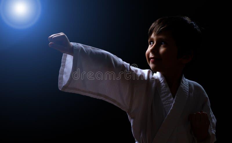 Gullig karatepojke i den vita kimonot som isoleras på mörk bakgrund Barnet som är klart för kampsporter, slåss Unge som slåss på  arkivbild