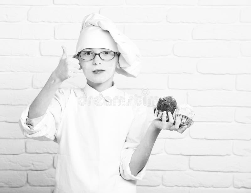 Gullig kockkock för ung pojke i den vita likformign och hatten på nedfläckat framsidamjöl med exponeringsglas som rymmer chokladk arkivbilder