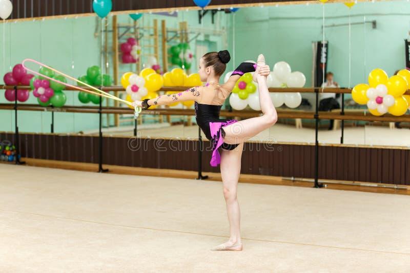 Gullig konstgymnastdans med banhoppningrepet arkivfoton