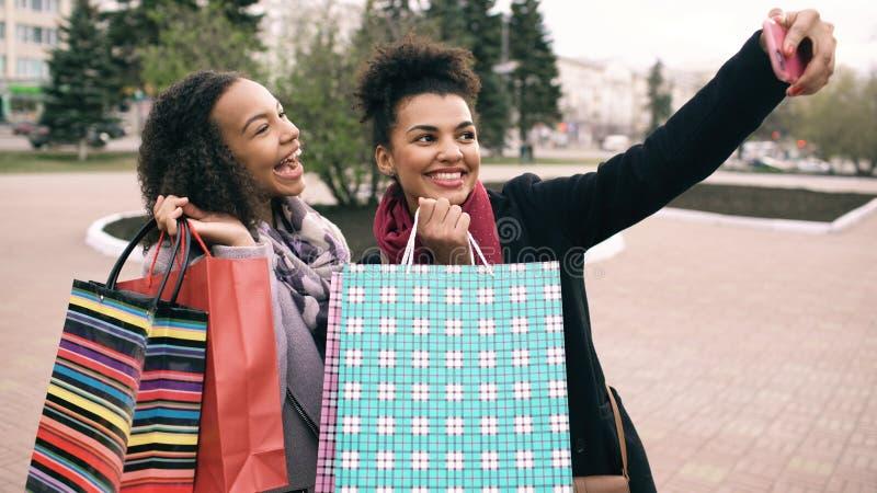 Gullig kvinna för afrikansk amerikan som två tar selfie med påsar och att le för shopping Vänner har gyckel, når de har besökt ga arkivbilder