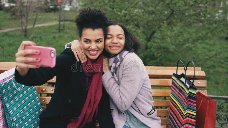 Gullig kvinna för afrikansk amerikan som två tar selfie på smartphonen med påsar och att le för shopping Flickvänner som sitter p arkivbilder